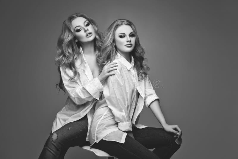 Δύο όμορφα κορίτσια στα άσπρα πουκάμισα και τα τζιν στοκ φωτογραφίες