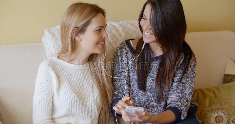Δύο όμορφα κορίτσια στον καναπέ ακούνε τη μουσική στοκ φωτογραφίες με δικαίωμα ελεύθερης χρήσης