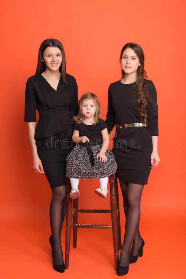 Δύο όμορφα νέα κορίτσια στα επιχειρησιακά κοστούμια και ένα μικρό κορίτσι μέσα στοκ εικόνα με δικαίωμα ελεύθερης χρήσης