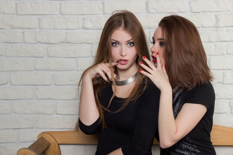 δύο όμορφα νέα κορίτσια στα μαύρα φορέματα κάθονται στον πάγκο και το κουτσομπολιό στοκ εικόνα