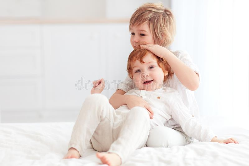 Δύο όμορφα παιδιά, αγκαλιά αδελφών, που παίζουν μαζί στο σπίτι στοκ εικόνα με δικαίωμα ελεύθερης χρήσης