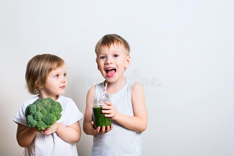 Δύο όμορφα παιδιά διασκέδασης με τους πράσινους καταφερτζήδες και το μπρόκολο Helthy στοκ εικόνα