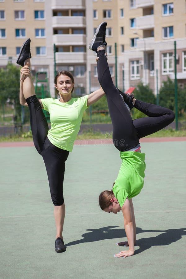 Δύο όμορφες γυναίκες που τεντώνουν στο πάρκο πόλεων μετά από να τρέξει και την αθλητική δραστηριότητα στοκ εικόνα με δικαίωμα ελεύθερης χρήσης
