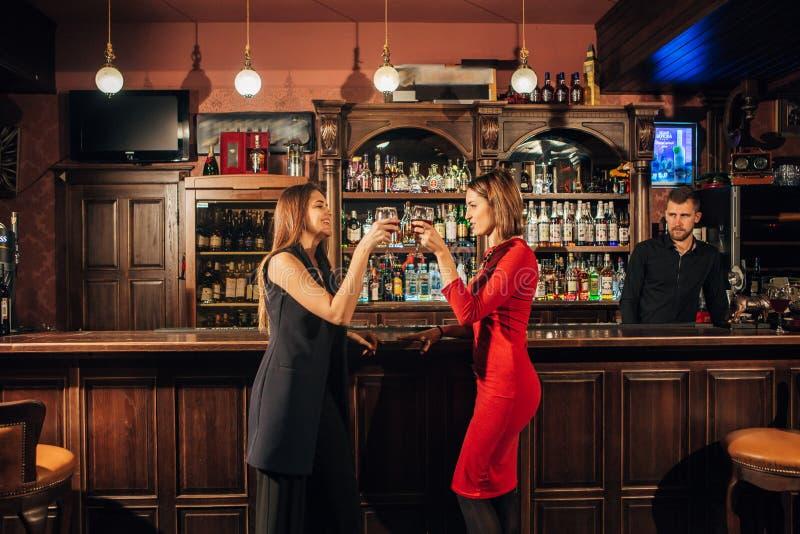 Δύο όμορφες γυναίκες χαλαρώνουν στο φραγμό στοκ φωτογραφία με δικαίωμα ελεύθερης χρήσης