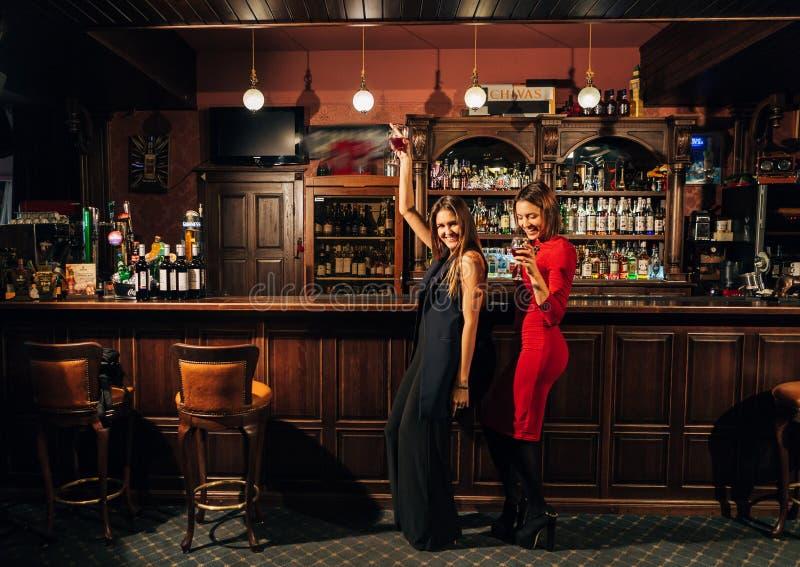 Δύο όμορφες γυναίκες χαλαρώνουν στο φραγμό στοκ φωτογραφία