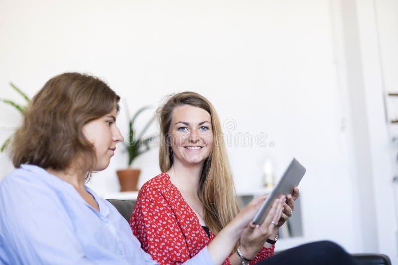 Δύο όμορφες νέες γυναίκες που κάθονται στο σπίτι στον καναπέ χρησιμοποιώντας έναν υπολογιστή και το χαμόγελο PC ταμπλετών στοκ εικόνα