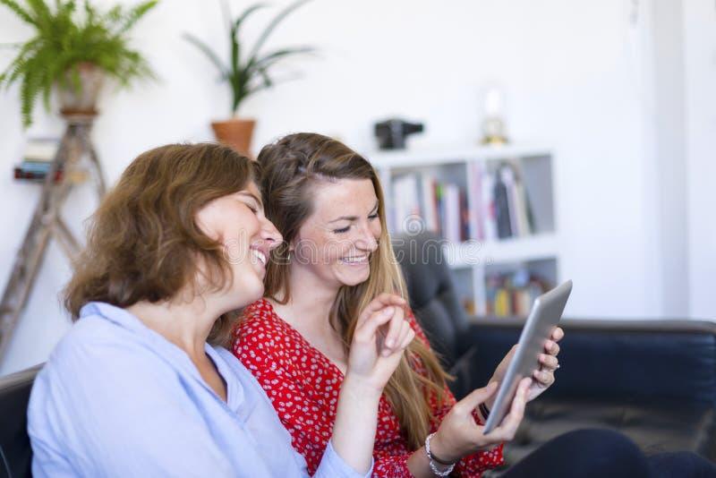 Δύο όμορφες νέες γυναίκες που κάθονται στο σπίτι στον καναπέ χρησιμοποιώντας έναν υπολογιστή και το χαμόγελο PC ταμπλετών στοκ φωτογραφία με δικαίωμα ελεύθερης χρήσης