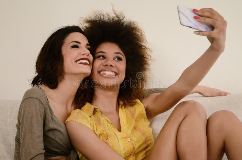 Δύο όμορφες φίλες κουτσομπολιού που παίρνουν selfie με το smartphone στοκ εικόνες