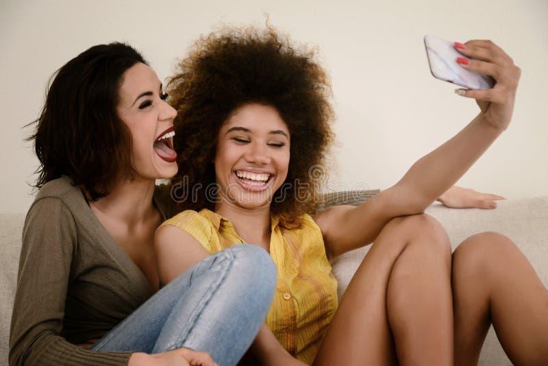 Δύο όμορφες φίλες κουτσομπολιού που παίρνουν selfie με το smartphone στοκ φωτογραφία