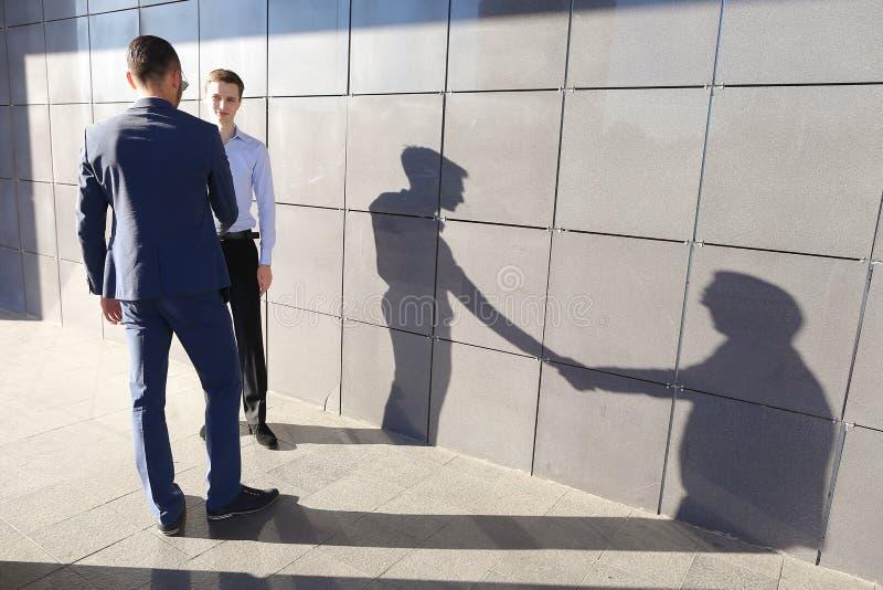 Δύο όμορφοι βέβαιοι επιχειρηματίες νεαρών άνδρων για να συναντηθεί και gree στοκ εικόνα