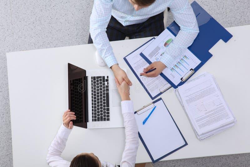 Δύο όμορφοι επιχειρηματίες τινάζουν τα χέρια τους, εργαζόμενος στην αρχή στοκ εικόνα