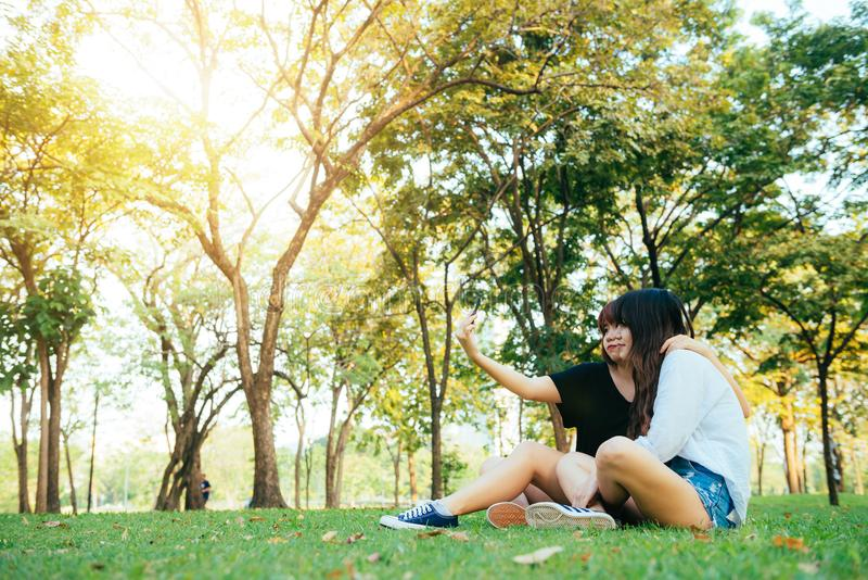 Δύο όμορφοι ευτυχείς νέοι ασιατικοί φίλοι γυναικών που έχουν τη διασκέδαση μαζί στο πάρκο και που παίρνουν ένα selfie στοκ εικόνες