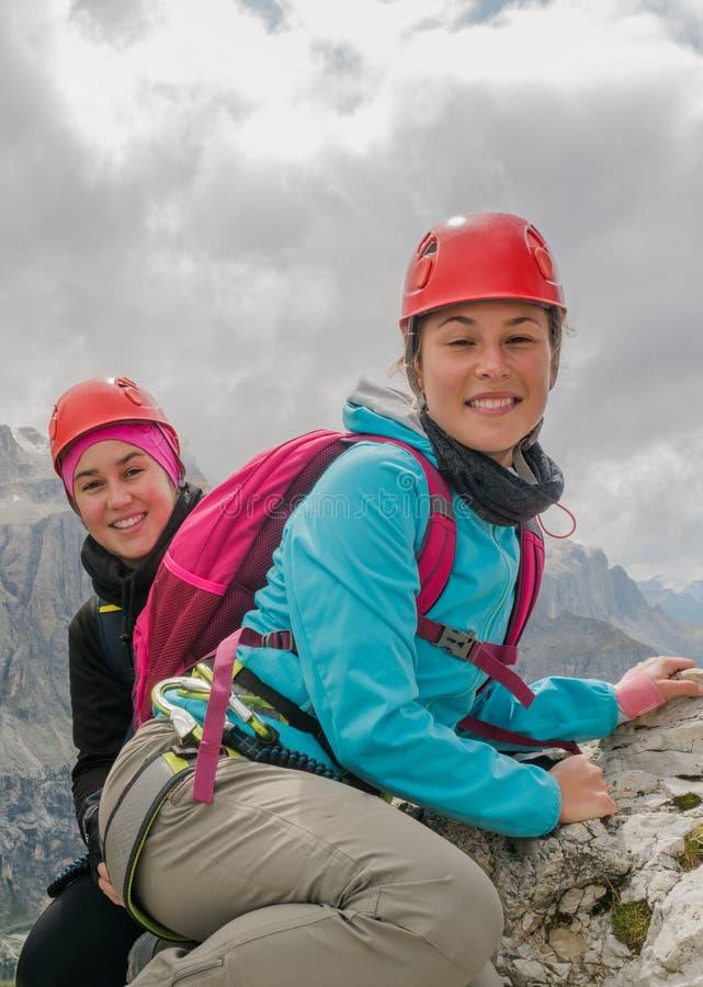 Δύο όμορφοι νέοι θηλυκοί ορειβάτες βουνών που χαμογελούν και τοπίο βουνών πίσω στοκ εικόνα