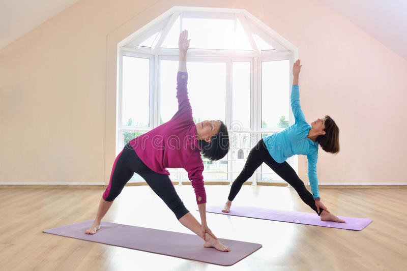 Δύο ώριμες γυναίκες που κάνουν την άσκηση γιόγκας στο στούντιο ικανότητας στοκ φωτογραφία με δικαίωμα ελεύθερης χρήσης
