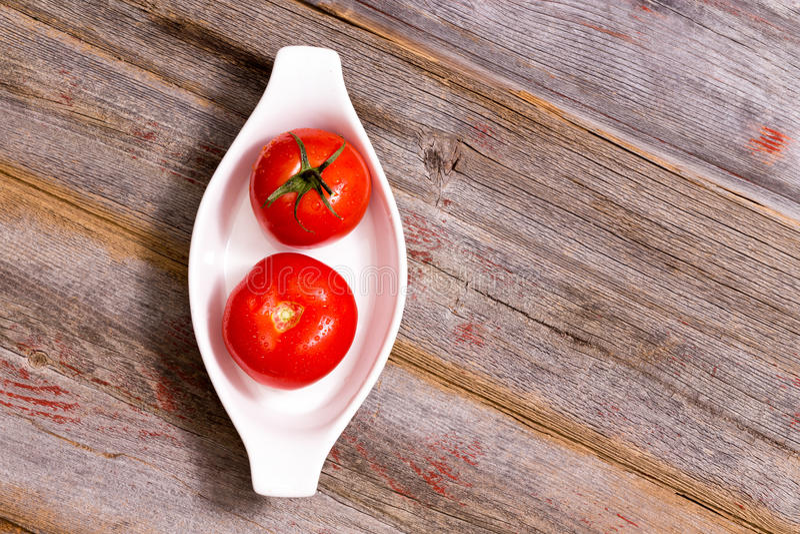 Δύο ώριμες κόκκινες ντομάτες σε ένα πιάτο στοκ εικόνες