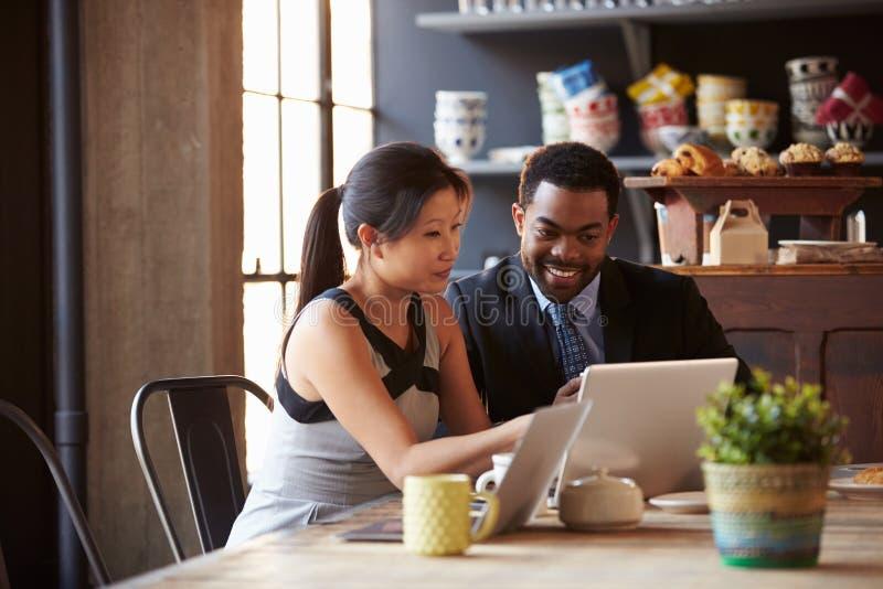 Δύο Businesspeople που λειτουργούν στο lap-top στον καφέ στοκ φωτογραφίες