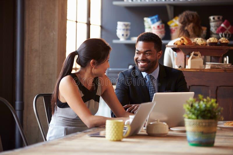 Δύο Businesspeople που λειτουργούν στο lap-top στον καφέ στοκ φωτογραφία