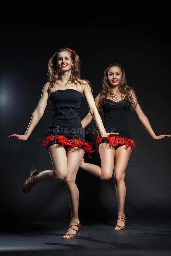 Δύο cabaret χορευτές στα φωτεινά κοστούμια πέρα από το σκοτάδι στοκ εικόνα με δικαίωμα ελεύθερης χρήσης