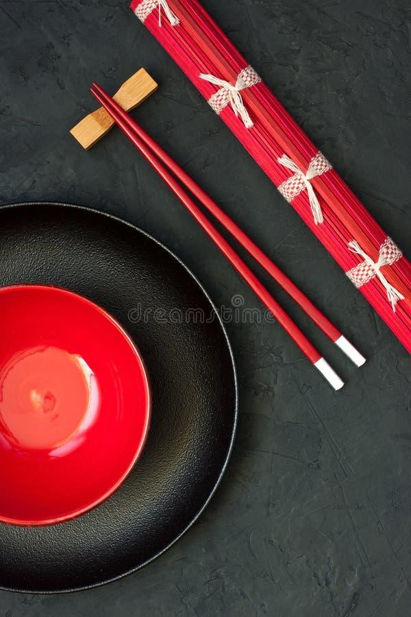 Δύο chopsticks δίπλα στο μαύρο και κόκκινο κύπελλο στοκ εικόνες με δικαίωμα ελεύθερης χρήσης