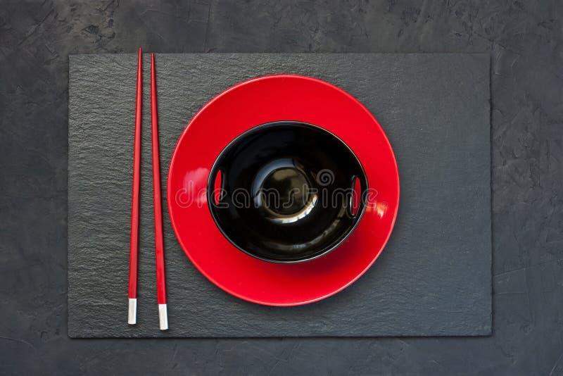 Δύο chopsticks δίπλα στο μαύρο και κόκκινο κύπελλο στοκ εικόνα