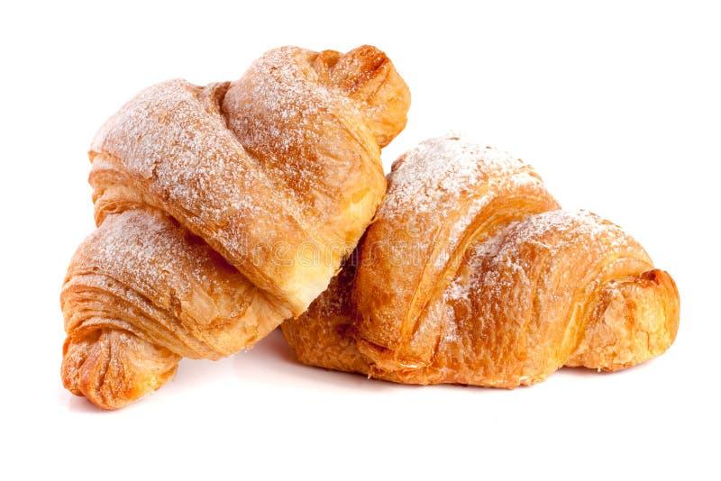 Δύο croissant που ψεκάζεται με την κονιοποιημένη ζάχαρη που απομονώνεται σε μια άσπρη κινηματογράφηση σε πρώτο πλάνο υποβάθρου στοκ φωτογραφίες με δικαίωμα ελεύθερης χρήσης