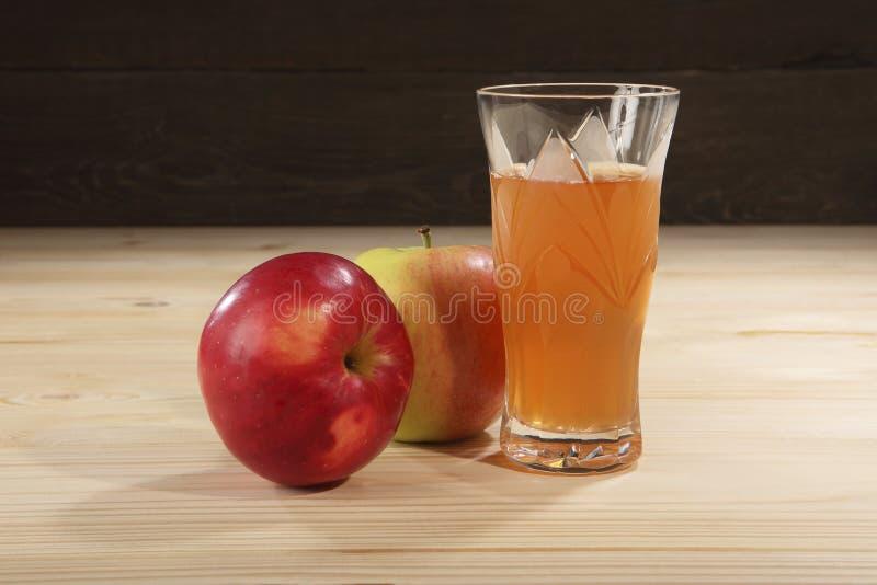 Δύο juicy, νόστιμα, ώριμα μήλα κοντά σε ένα γυαλί κρυστάλλου με τον πρόσφατα συμπιεσμένο χυμό σε έναν ξύλινο πίνακα Κινηματογράφη στοκ φωτογραφίες