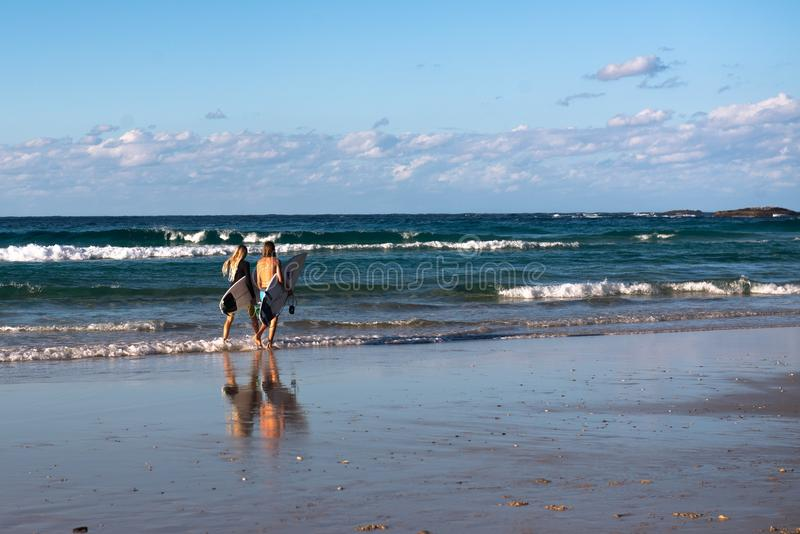 Δύο surfers που περπατούν σε μια αυστραλιανή παραλία στοκ εικόνες