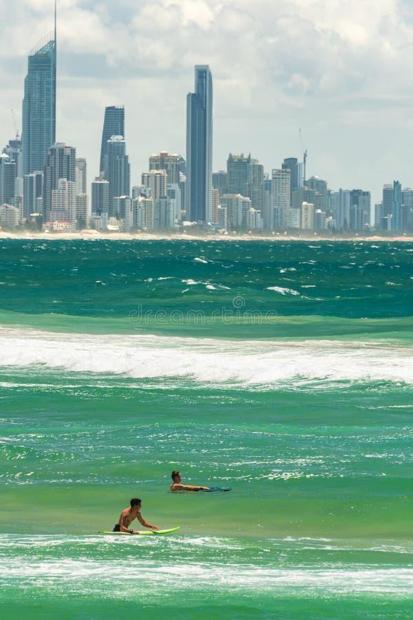 Δύο surfers στο νερό με τη εικονική παράσταση πόλης Gold Coast στο υπόβαθρο στοκ εικόνες