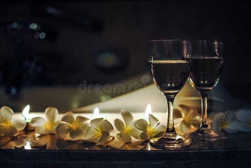 Δύο wineglasses με τα λουλούδια και τα κεριά στοκ φωτογραφίες