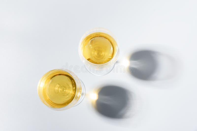 Δύο wineglasses του άσπρου κρασιού με τις σκιές στο γκρίζο υπόβαθρο r Έννοια εορτασμού διακοπών στοκ φωτογραφίες με δικαίωμα ελεύθερης χρήσης