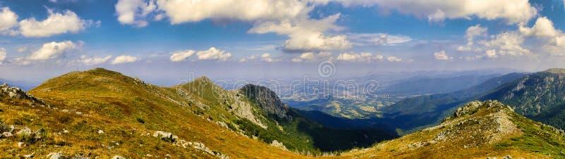 Δύσκολες αιχμές βουνών κάτω από το μπλε ουρανό με τα άσπρα σύννεφα πανοραμικά στοκ εικόνα