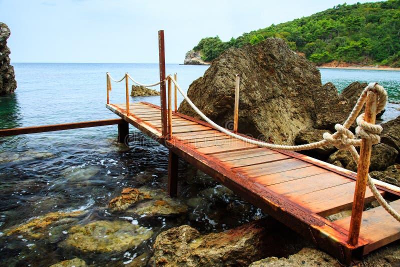 Δύσκολη αδριατική παραλία και ξύλινη αποβάθρα στοκ φωτογραφία με δικαίωμα ελεύθερης χρήσης