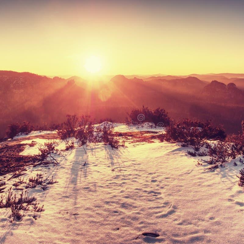 Δύσκολη αιχμή βουνών με το χιόνι και ουρανός με τον καυτό ήλιο το χειμώνα στοκ φωτογραφίες
