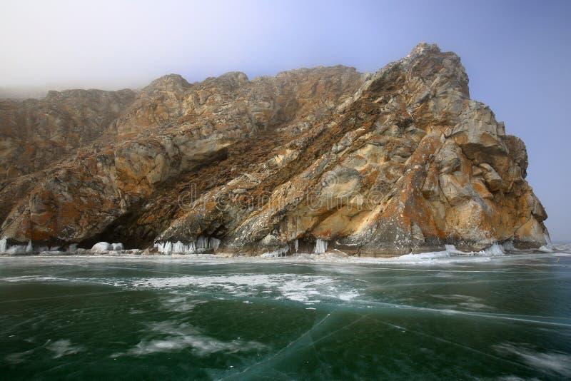 Δύσκολη ακτή της λίμνης Baikal στην ομίχλη το χειμώνα στοκ φωτογραφία