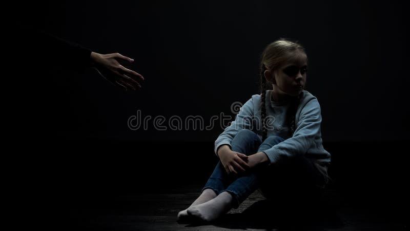 Δύσπιστη συνεδρίαση μικρών κοριτσιών στο σκοτεινό δωμάτιο που αρνείται το ενήλικο χέρι βοηθείας, φόβος στοκ φωτογραφίες
