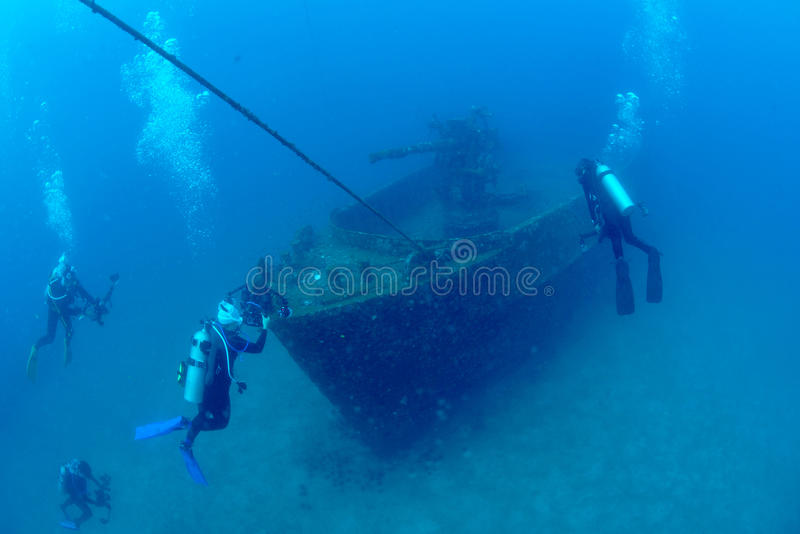 Δύτες που εξερευνούν τα συντρίμμια σκαφών στην τροπική θάλασσα στοκ φωτογραφία