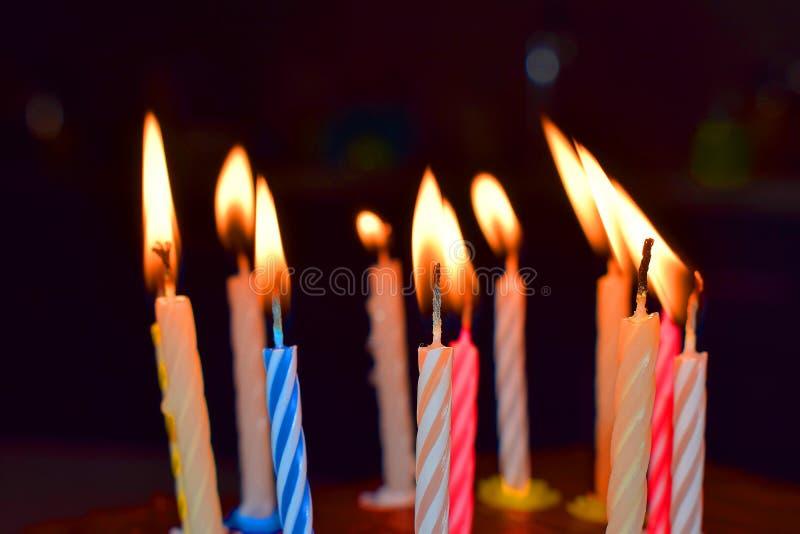 Δώδεκα ζωηρόχρωμα αναμμένα κεριά γενεθλίων στοκ εικόνα