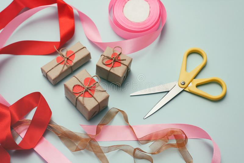 Δώρα που τυλίγουν τη διαδικασία Διακοσμητικό έγγραφο, κορδέλλες μεταξιού, κιβώτια δώρων, ψαλίδι Ανοικτό μπλε υπόβαθρο στοκ εικόνες