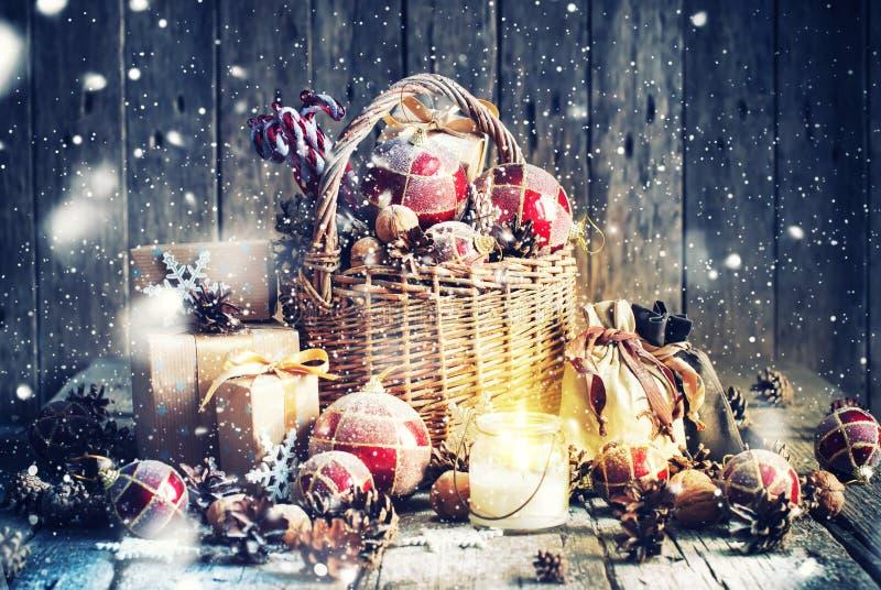 Δώρα Χριστουγέννων στο καλάθι και το καίγοντας κερί κόκκινος τρύγος ύφους κρίνων απεικόνισης στοκ εικόνα