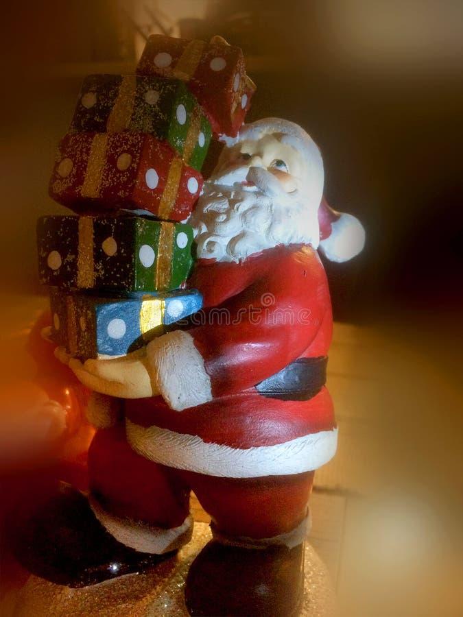 δώρα Claus που κρατούν το νέο statuette santa του s έτος στοκ εικόνα