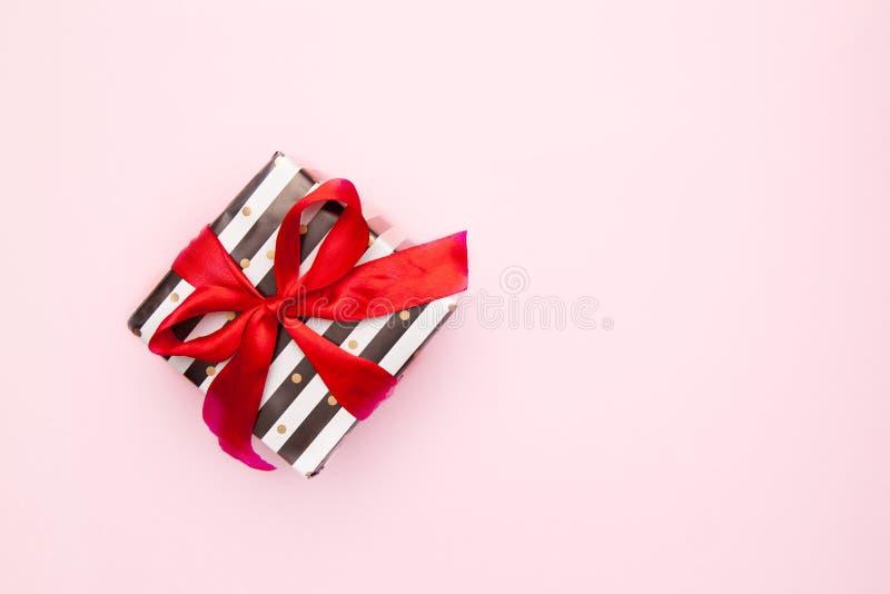 Δώρο ή παρόν κιβώτιο στα άσπρα και μαύρα λωρίδες με ένα κόκκινο τόξο κορδελλών που απομονώνεται στη ρόδινη άποψη επιτραπέζιων κορ στοκ φωτογραφίες