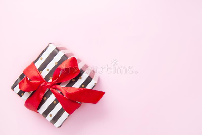 Δώρο ή παρόν κιβώτιο στα άσπρα και μαύρα λωρίδες με ένα κόκκινο τόξο κορδελλών που απομονώνεται στη ρόδινη άποψη επιτραπέζιων κορ στοκ φωτογραφία με δικαίωμα ελεύθερης χρήσης