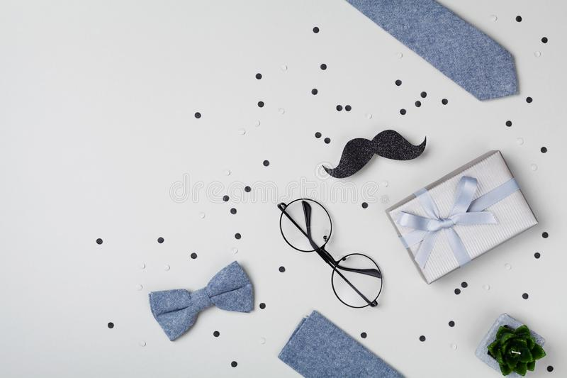 Δώρο ή παρόν κιβώτιο, bowtie, moustache, γυαλιά και κομφετί για την ευτυχή ημέρα πατέρων Η τοπ άποψη και επίπεδος βάζει στοκ εικόνες