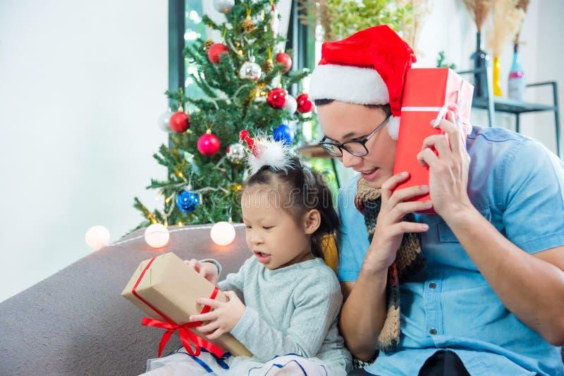 Δώρο ημέρας των Χριστουγέννων ανοίγματος κοριτσιών με τον πατέρα της στον καναπέ στοκ εικόνες