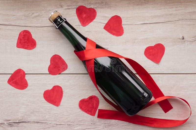 Δώρο, η καρδιά και το μπουκάλι του κόκκινου κρασιού για ρομαντικό ημερησίως βαλεντίνων ` s διακοπών στοκ φωτογραφίες