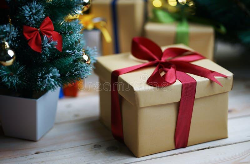 Δώρο κιβωτίων Χριστουγέννων εκτός από το μικρό χριστουγεννιάτικο δέντρο στοκ φωτογραφία