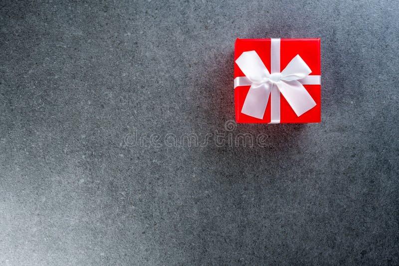 Δώρο Χριστουγέννων ή νέο έτος με την άσπρη κορδέλλα στο σκοτεινό υπόβαθρο με το κενό διάστημα για το κείμενο, πρότυπο, πρότυπο χε στοκ φωτογραφίες