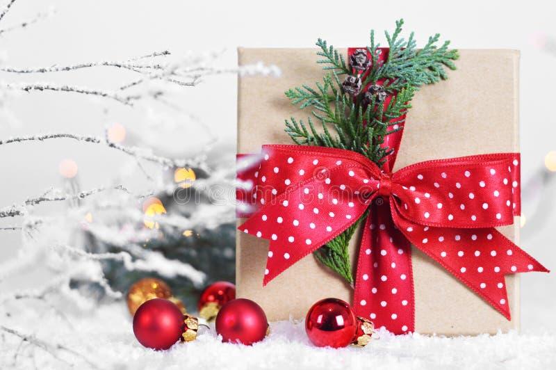 Δώρο Χριστουγέννων με την κόκκινη κορδέλλα και κόκκινες σφαίρες Χριστουγέννων στο χιόνι στοκ φωτογραφία με δικαίωμα ελεύθερης χρήσης