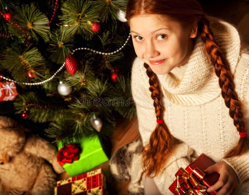 Δώρο Χριστουγέννων, νέα γυναίκα κοντά στο δέντρο στοκ φωτογραφίες