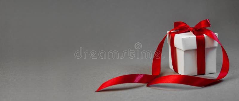 Δώρο Χριστουγέννων στο άσπρο κιβώτιο με την κόκκινη κορδέλλα στο σκοτεινό γκρίζο υπόβαθρο Νέο έμβλημα σύνθεσης διακοπών έτους διά στοκ εικόνες